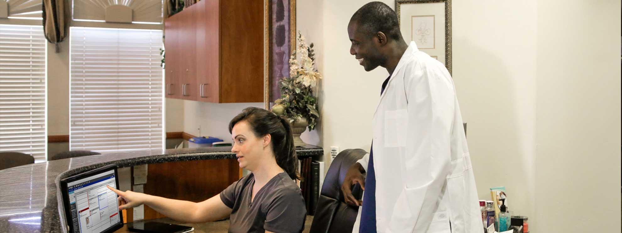 Image of office manager training dentist on dental software